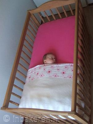 Baby in kort opgemaakt bed