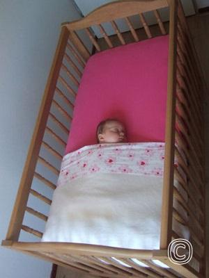 Baby slaapt veilig in een kort opgemaakt ledikant, laken overdwars en baby voldoende hoog toedekken